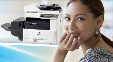 Woman sitting by a printer copier that is provided by Wisconsin Copy and Business Equipment
